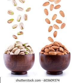 Almonds and Pistachios falling to wooden bowl.