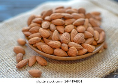 Almonds in a plate on burlap.