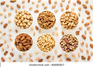 Almonds, roasted and raw pistachios, dried walnuts, roasted hazelnuts, salted peanuts in 6 white bowls in 2 rows of 3 each on white background of scattered nuts. 6 nuts types. Horizontal. Top view.