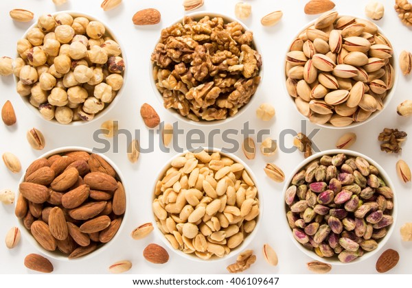 Almonds, roasted and raw pistachios, dried walnuts, roasted hazelnuts, salted peanuts in 6 white bowls in 2 rows of 3 each on white background of scattered nuts. Close 6 nuts types. Top view.