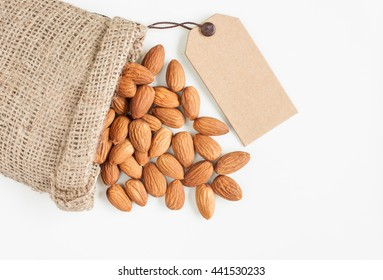 almonds, almonds in sack with a price tag on over white background, top view