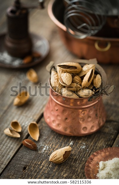Almonds in the shell. Copper vintage kitchenware, rustic style. Copy space. Vintage crockery. The mysterious atmosphere