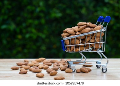Almonds in shopping cart on wooden table with nature green background,copy space.