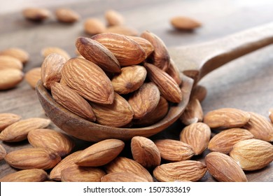 almonds in a spoon on a wooden table close-up