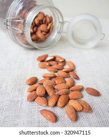 Almonds spread from the jar on the ground.