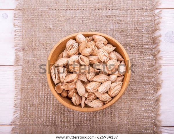 Almonds in their skins and peele in brown bowl on wooden background. Healthy food
