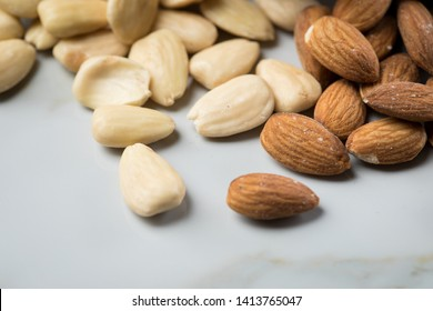 Almonds as unpeeled kernel and blanched peeled nut on marble background