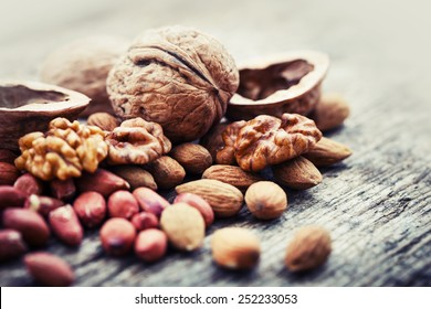 Almonds, walnuts and hazelnuts on wooden table / assortment of nuts