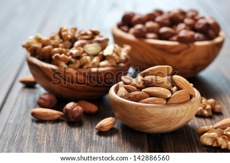 Almonds, walnuts and hazelnuts in wooden bowls  on wooden background