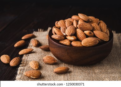 Almonds in a wooden bowl on dark wooden table, Almond  background with copy space