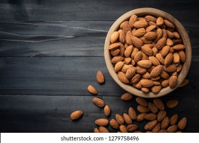 Almonds in wooden bowl on dark wood table. Almond concept with copyspace.topview.