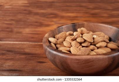 Almonds in wooden bowl on dark background.