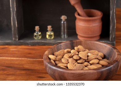 Almonds in wooden bowl on dark background with glass bottles - almond's oil