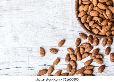 Almonds in wooden bowl on wihte background.