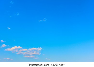 Almost clear blue sky with clouds - background with large copyspace