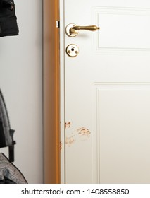 Almost closed bathroom door with a chocolate hand mark from a child.