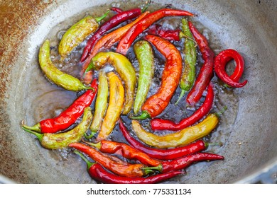 Almost cooked red and green chilies frying in oil