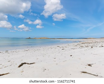 An almost desterted beach near Landeda, Brittany, at low tide. Light clouds float in a blue sky.