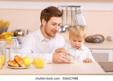 Almost done. Caring father softly helps his little child to eat up a cereal.