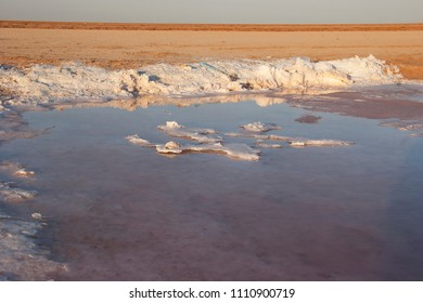 almost dried up lake in the desert with salt deposits on the bottom in sallow water pool, pilling up salt
