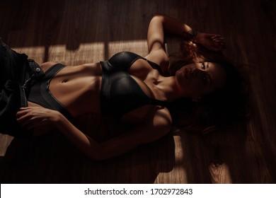 Mujer casi desnuda y lisa, en forma posando en el luminoso apartamento iluminado con luz del sol, sacándose sus jeans negros mientras usa ropa interior deportiva, luciendo sexy.