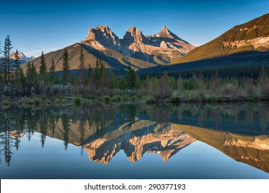 Almost near perfect reflection of the Three Sisters Peaks in the Bow River.  Near Canmore, Alberta Canada
