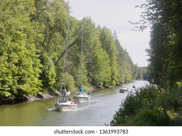 ALMSTA, SWEDEN - JUL 09 2018: Several sailships on a narrow canal Vaddo kanal through the forest. July 09, 2018, Almsta, Sweden