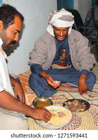 AL-MUKALLA, YEMEN - DECEMBER 2008: unidentified men eat with hands on the ground with crossed legs on December 24, 2008 in al-Mukalla. Yemenis are happy when tourists make photos from them