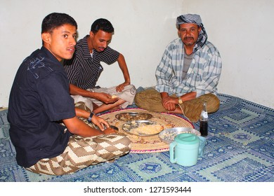 AL-MUKALLA, YEMEN - DECEMBER 2008: unidentified men eat with hands on the ground with crossed legs on December 24, 2008 in al-Mukalla. Yemenis are happy when tourists make photos from them.
