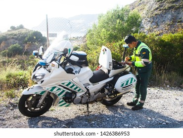 Almunecar, Andalucia, Spain - November 3rd, 2018 - Spanish Police officer writing ticket for motor offence