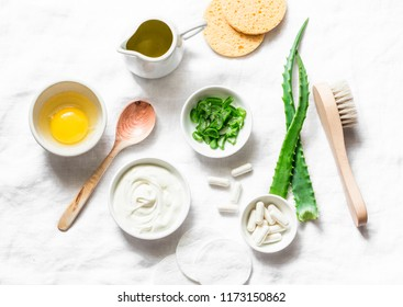Aloe face mask ingredients -aloe, yogurt, egg, olive oil and beauty accessories on light background, top view. Home recipe. Flat lay
