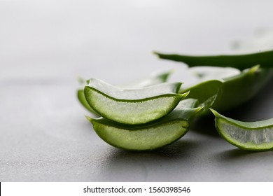 Aloe vera fresh leaves and sliced on grey background. copy space. close up