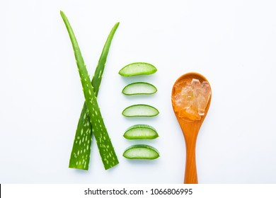Aloe vera fresh leaves with slices and gel on wooden spoon. isolated over white. Aloe vera is a popular medicinal plant that is used for health and beauty.