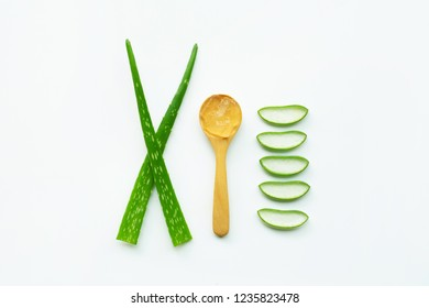 Aloe vera fresh leaves with slices and aloe vera gel on wooden spoon. isolated on white