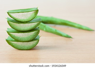 Aloe vera fresh leaves and slices with water drops on wooden background, closeup