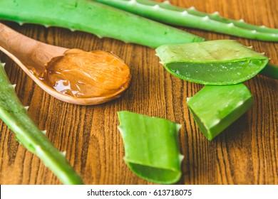 Aloe vera gel on wooden spoon with aloe vera on wooden table. Selective focus