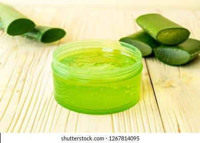 aloe vera gel with aloe sliced on wood background