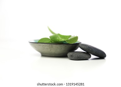 aloe vera leaves in a small bowl, with spa stones on a white background