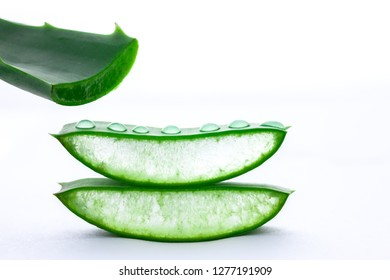 Aloe vera in pieces and drops in front of white background