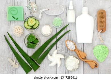 Aloe vera skin care including plant stems, cucumber, yoghurt, moisturiser, facial cream, body lotion and exfoliating salt scrub. Health concept beneficial for sunburn, psoriasis, eczema and acne.