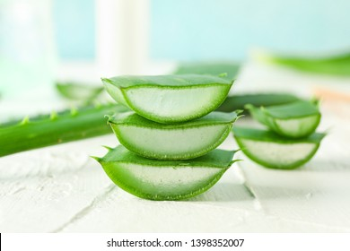 Aloe vera slices on white wooden table, closeup and space for text. Natural treatment