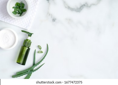 Aloe vera spa treatment concept. Top view green bottle with aloe vera gel, hand cream and sliced stems aloe vera on marble background. Organic natural skincare products