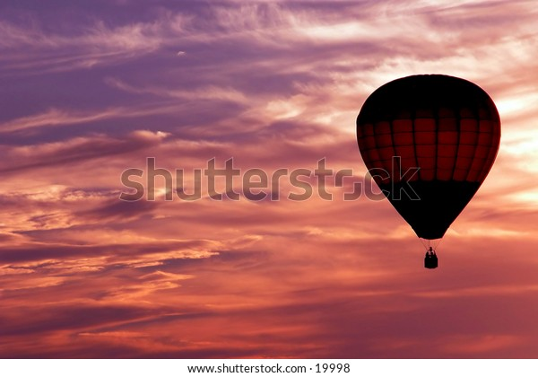 Aloft In Evening Color: Beautiful evening sky with offset hot air ballon.
