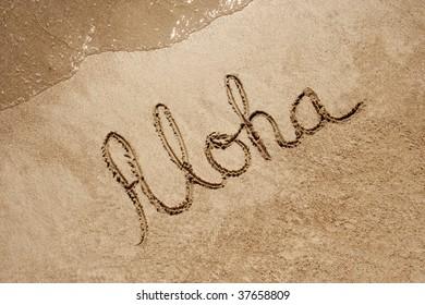 Aloha handwritten in sand on a beach