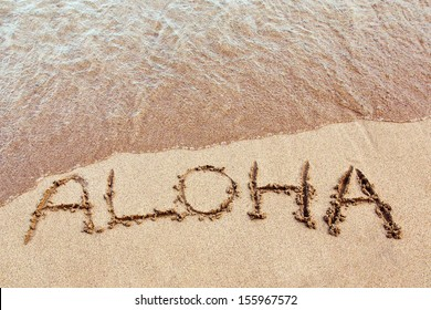 aloha written in the sand on a Hawaiian beach