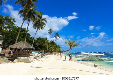 Alona Beach, Bohol - Philippines - February 04, 2015: A native beach hut looks out over the turquoise sea and countless tour boats. Bohol is a famous tourism hotspot.