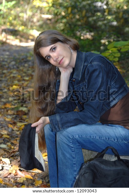 Alone for an afternoon in the park.  Female teen sits on a park bench with her book bag.  She is holding navy cap.