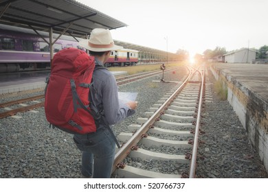 Alone backpacker and hat at the train station and looking on the map for plan to travel.  Travel concept.