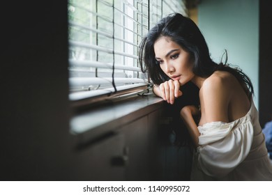 Alone beautiful woman sitting on window