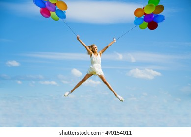 Alone blond Woman Jumping with colorful balloons for Joy. One happy slim girl fly against blue summer sky with clouds. Idea of success, growth , light, diet, luck, freedom, anorexia